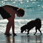 Outer Banks Vacation Guide - Young boy and dog on beach